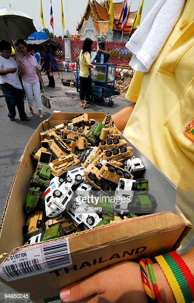 A teenage Thai entrepreneur sells miniature plastic tanks for 25 Baht or 67 US cents a piece to the people watching Thai soldiers and tanks deployed...