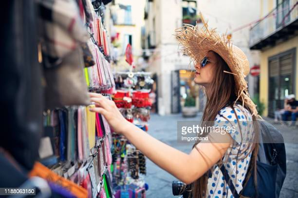 teenage tourist girl browsing smartphone cases at street shop in italy - phone cover stock pictures, royalty-free photos & images