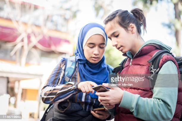 Teenage tourists using smartphone for searching location in city