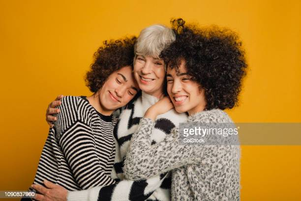 teenage twins embracing their mother - studio shot stock pictures, royalty-free photos & images