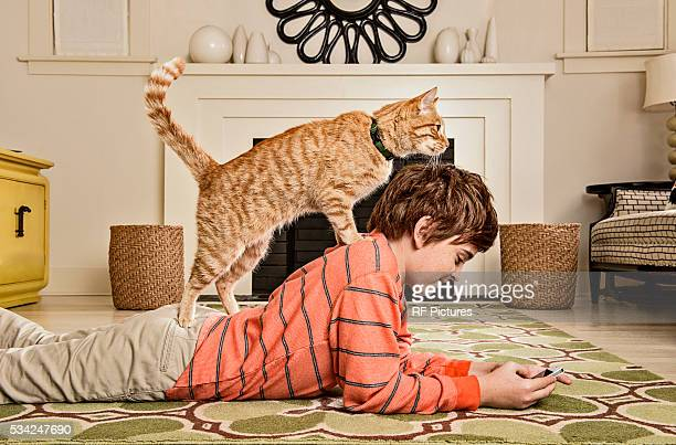 Teenage (13-15) using cell phone with cat on back