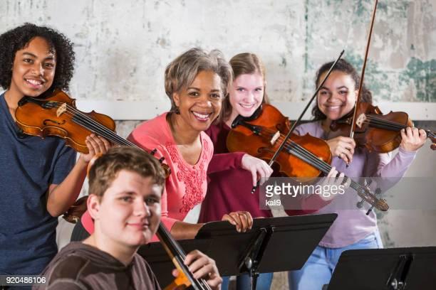 Teenage violinists with music teacher