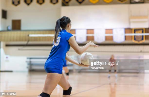 teenage volleyball player prepares to serve... - high school volleyball stock photos and pictures