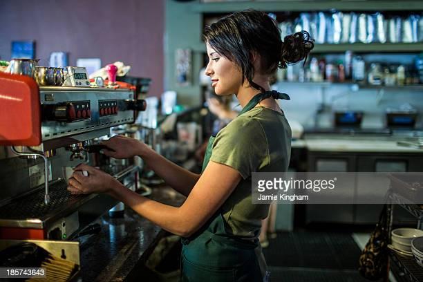 Teenage waitress preparing coffee in cafe kitchen