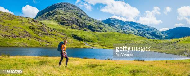teenage woman hiker with backpack walking beside mountain lake panorama - wilderness stock pictures, royalty-free photos & images
