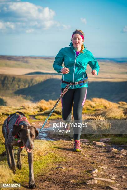 teenage woman trail running on mountain path with canicross dog - german shorthaired pointer stock pictures, royalty-free photos & images