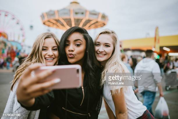 teenage women friend group enjoying state fair - puckering stock pictures, royalty-free photos & images