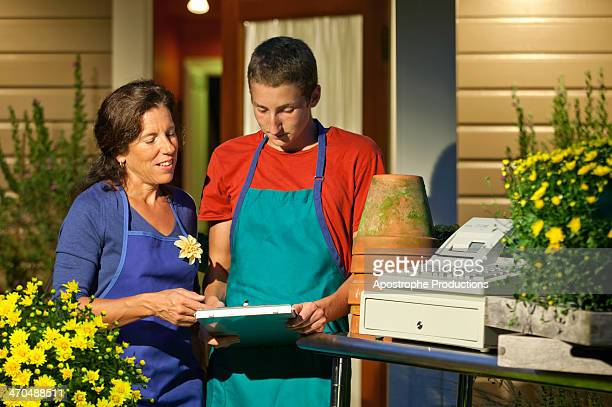 teenage worker getting instructions at florist. - blacksburg stock pictures, royalty-free photos & images