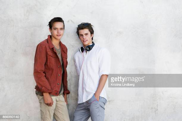 teenage/ young adult friends portraits by a grey wall - ポケットに手を入れている ストックフォトと画像