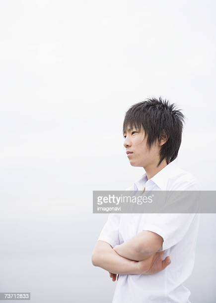 teenageboy looking far with crossed arms - 少年 ストックフォトと画像