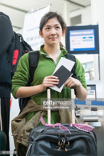 teenaged asian girl with passport, backpack and luggage at airport - vancouver international airport stock pictures, royalty-free photos & images