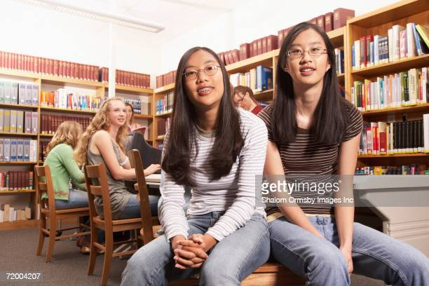 Teenaged Asian girls sharing chair in library