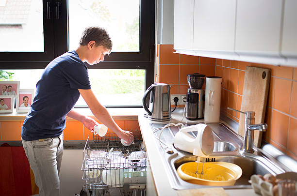 Teenaged boy filling the dishwasher with dirty dishes on August 12 in Duelmen, Germany. Photo by Ute Grabowsky/Photothek via Getty Images)
