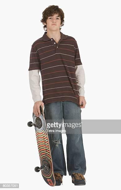 Teenaged boy holding skateboard
