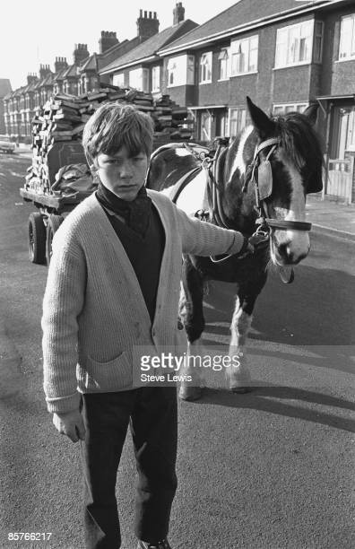 A teenaged boy leads a horsedrawn cart down a street in the East End of London 1960s