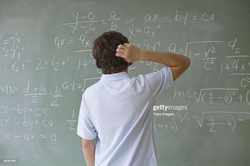 Teenaged boy looking at math equations on blackboard : Stock Photo