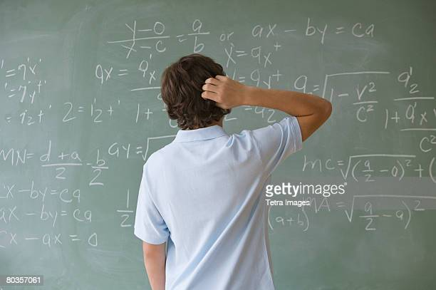 Teenaged boy looking at math equations on blackboard
