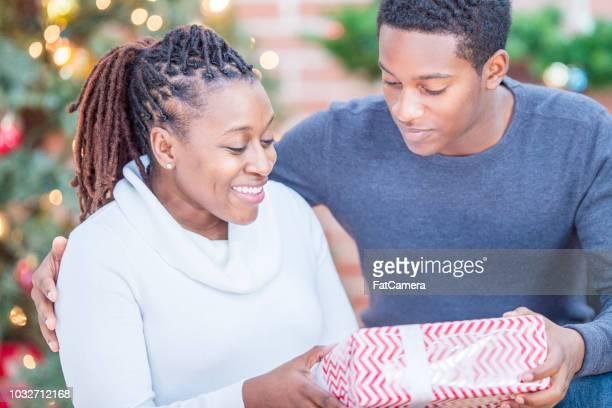十代の少年彼の母親をクリスマスのギフトと幸せになります - ギフトラウンジ ストックフォトと画像