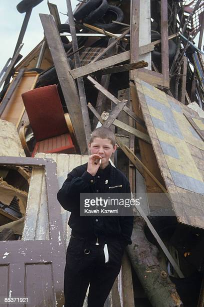 A teenaged boy smokes a cigarette in a scrapyard in Catholic west Belfast 17th September 1985