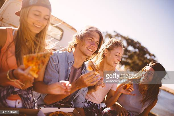 Teenaged friends sitting together outside eating pizza