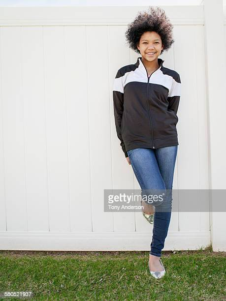 Teenaged girl leaning on fence in back yard