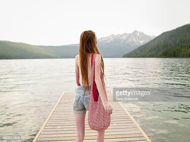 Teenaged girl on dock at mountain lake