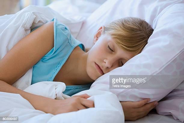 Teenaged girl sleeping in bed