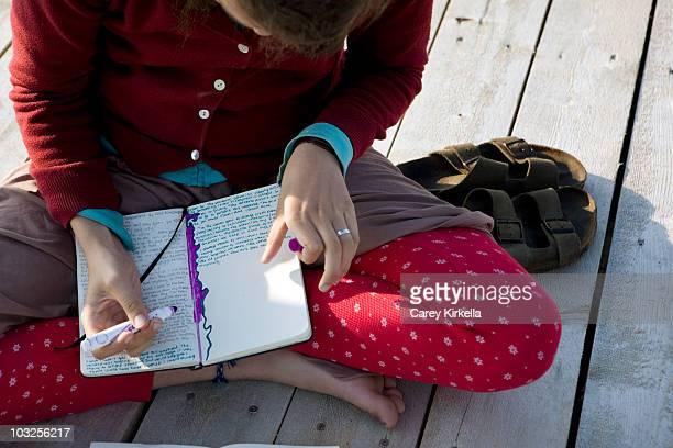 Teenaged girl writing in a journal