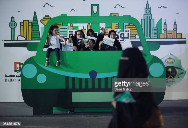 Teenaged girls pose behind a pretend car while they old up certificates for completing an outdoor educational driving event for women on June 22 2018...