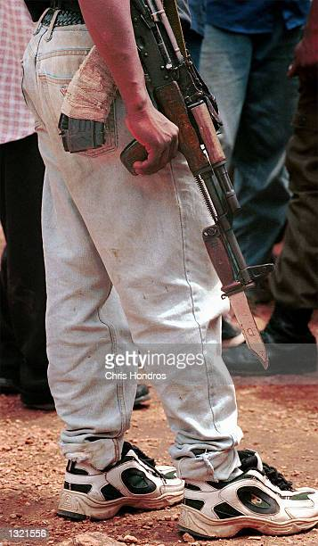 A teenaged RUF rebel soldier holds his weapon down during a rally June 9 2001 in the eastern town of Buedo Sierra Leone The RUF infamous for their...