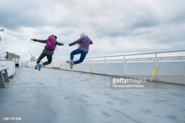 teenaged sisters jumping in unison on ferry deck, canada - ferry stock photos and pictures