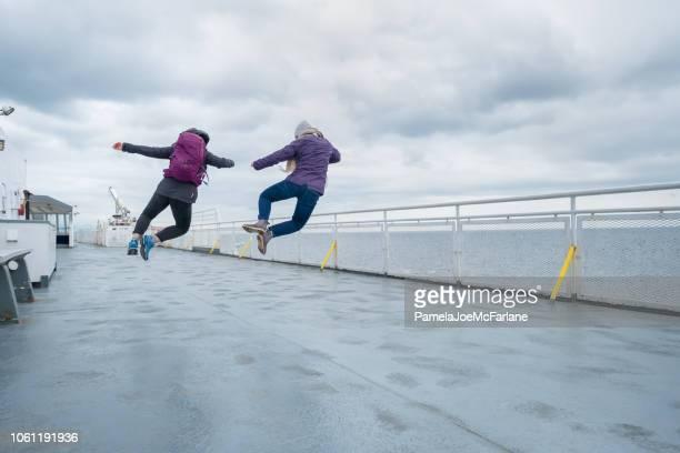 sœurs adolescentes sautant à l'unisson sur le ferry pont, canada - ferry photos et images de collection