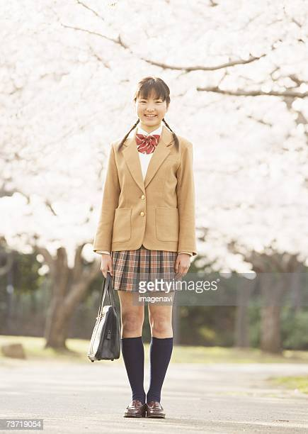 Teenagegirl standing under tree of cherry blossom