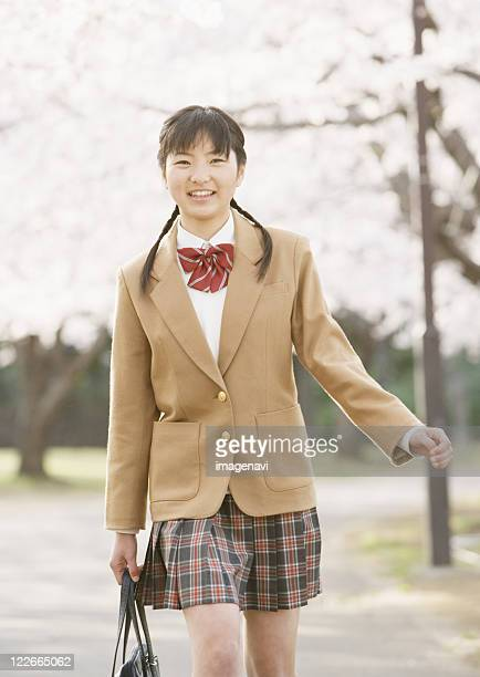 teenagegirl walking under cherry blossom trees - asian miniskirt stock photos and pictures