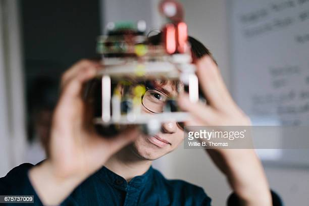 teenager admiring homemade robot - innovation stock-fotos und bilder