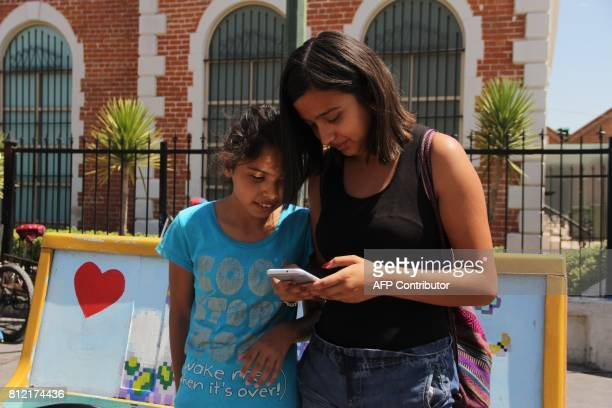 A teenager and a girl look at a new app released by Ciudad Juarez's municipality to help women in risk send alert calls in Ciudad Juarez Mexico on...