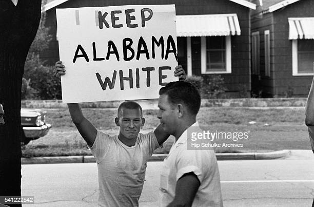 Teenager and an adult during a protest against school integration in Montgomery, Alabama, USA, 1963. The youth holds a placard reading 'Keep Alabama...