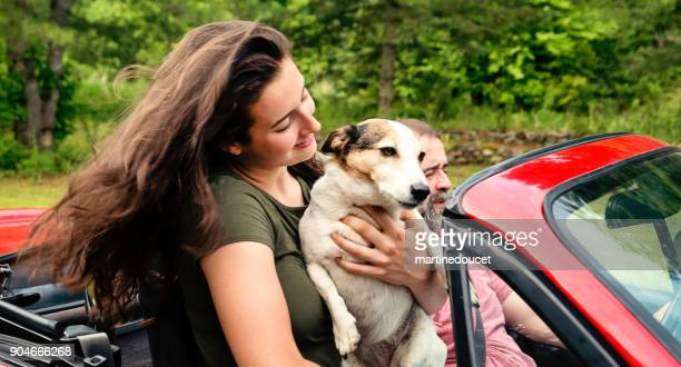 Teenager and dog enjoying a ride in red convertible car.