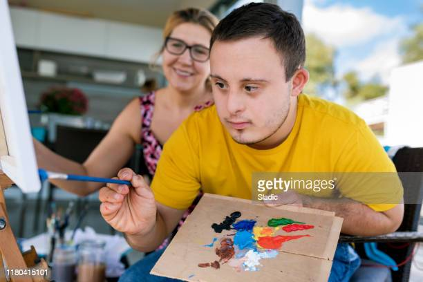 teenager artist with down syndrome - prop stock pictures, royalty-free photos & images