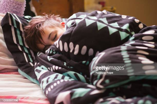 Teenager asleep and wrapped in a blanket.