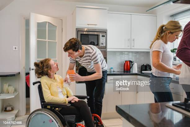 teenager assisting his disabled sister in the kitchen - epilepsy stock pictures, royalty-free photos & images