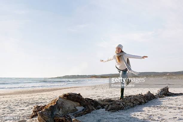 Teenager balancing on tree on beach in winter