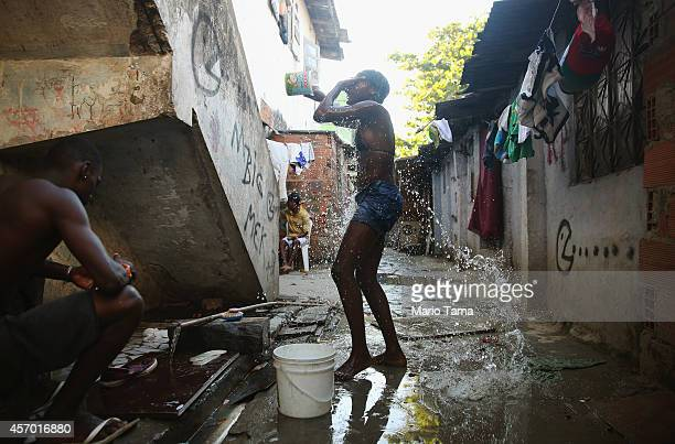 A teenager bathes with water collected from one running pipe in an impoverished section of the occupied Complexo da Mare one of the largest favela...