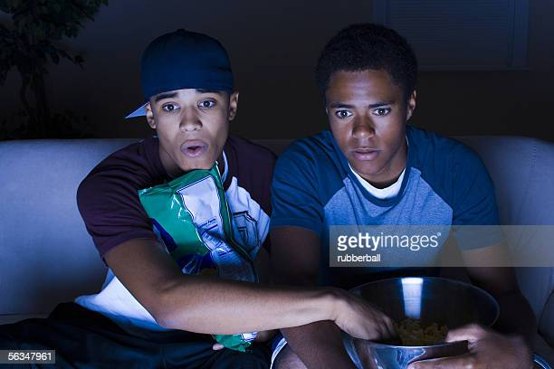 Teenager boy and a young man watching television