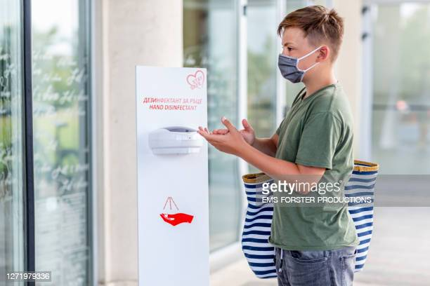 teenager boy is wearing a homemade protective mask while he is using hand disinfectant - 消毒薬 ストックフォトと画像