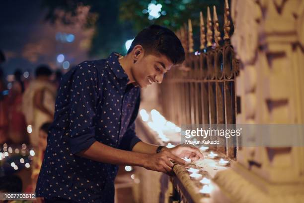 teenager boy lighting lamp during diwali festival - diwali celebration stock photos and pictures