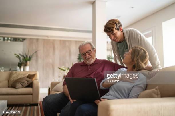 祖父母とノートブックを使用するティーンエイジャーの少年 - 家族の集まり ストックフォトと画像