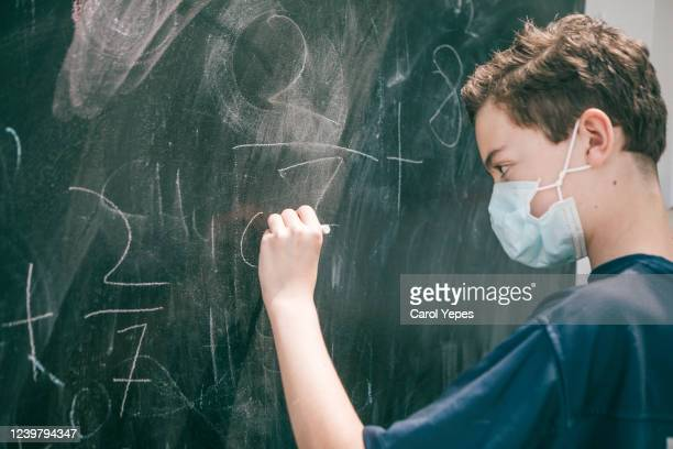 teenager boy wearing protective mask at school - 教育 ストックフォトと画像