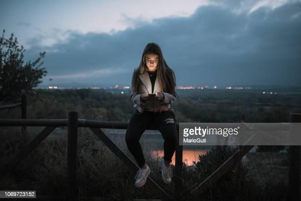 teenager checking her smartphone - meninas adolescentes imagens e fotografias de stock