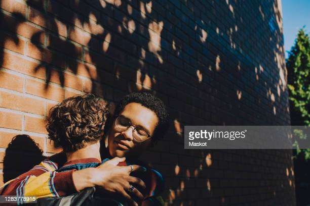 teenager consoling friend while embracing against brick wall - generation z stock pictures, royalty-free photos & images